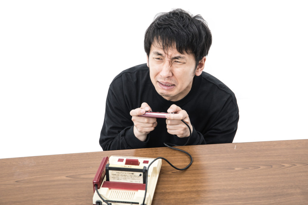 ファミコンを握って難しい顔をする男性